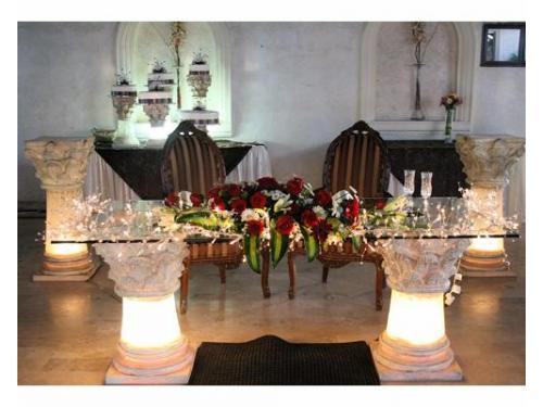 Iluminación y arreglo floral en la mesa de los novios